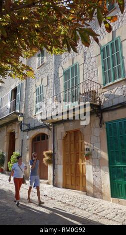 Tourists walking in a street of the touristic majorcan city of Valldemossa. Majorca, Spain, Europe. - Stock Photo