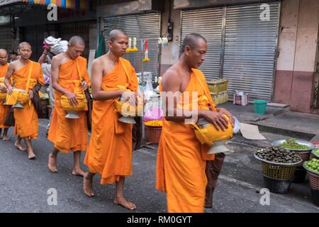 Morning round of buddhist monks begging for alms at Nora street market, Hatyai, Thailand - Stock Photo
