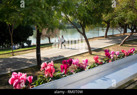 A young couple walking beside the Guadalquivir river on a warm February day in Seville, Spain - Stock Photo