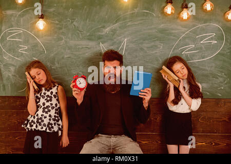 Teacher and girls pupils in classroom, chalkboard on background. Children and teacher with drawn by chalk horns. Man with beard shouting while - Stock Photo