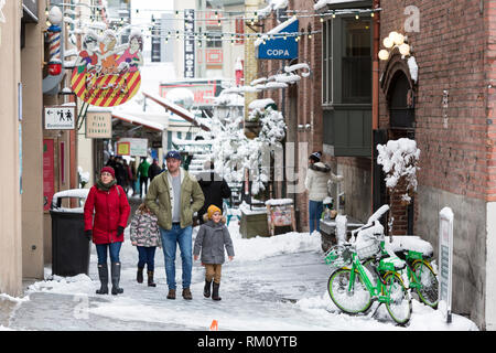 Seattle, Washington: Visitors walk along Post Alley at Pike Place Market as a strong winter storm blankets the city in six inches of snow. - Stock Photo