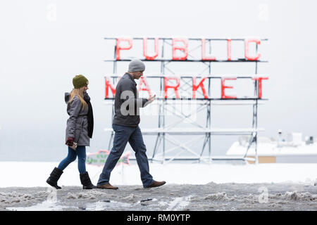 Seattle, Washington: A young couple crosses Pine Street at Pike Place Market as a strong winter storm blankets Seattle in six inches of snow. - Stock Photo