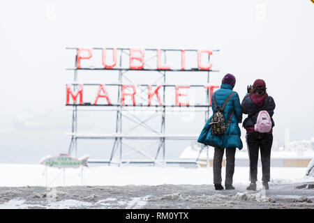 Seattle, Washington: Visitors stop to take a photo  of Pikes Place Market as a strong winter storm blankets Seattle in six inches of snow. - Stock Photo