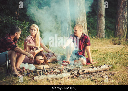 Group of friends camping in forest. People having fun talking around campfire. Cooking sausages over the fire - Stock Photo