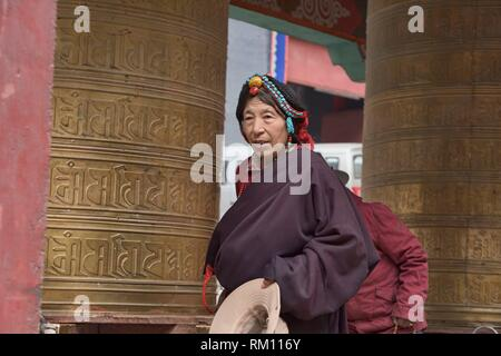Tibetan pilgrim spins a prayer wheel outside the holy Bakong Scripture Printing Press Monastery in Dege, Sichuan, China. - Stock Photo