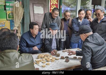 Old men playing Xiangqi, Chinese chess, Jiayuguan, Gansu, China. - Stock Photo