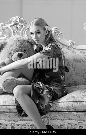 Lovely blond girl hugging huge teddy bear while sitting on retro sofa. Slim woman in flowery gray dress in her room - Stock Photo