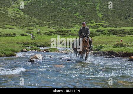 Kyrgyz horserider crossing the Tup River, Jyrgalan Valley, Kygyzstan. - Stock Photo