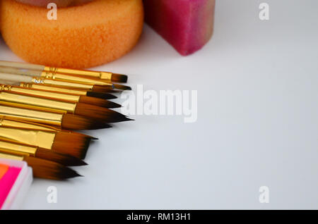 Color cosmetics, brushes and sponges for face painting on white background. Children party concept - Stock Photo