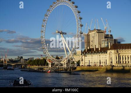 The London Eye and the County Hall on Queen's Walk. On the left, a view of the Hungerford and the Golden Jubilee bridges over the river Thames. - Stock Photo