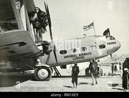 """Imperial Airways Handley-Page HP 42 biplane 'Hanno', Gwadar, Baluchistan, c1931-c1940 (1946). 'By 1929, Imperial Airways Ltd. had pushed their regular weekly service from Great Britain to India. The leisurely four-engined biplane 'Hanno' was typical of the land-based passenger aircraft of those days. She is at Gwadar, Baluchistan. From """"Merchant Airmen - The Air Ministry Account of British Civil Aviation, 1939-1944"""". [His Majesty's Stationery Office, London, 1946]. - Stock Photo"""