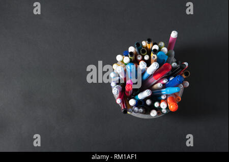 pens pens pencils in a plastic jar on a dark background - Stock Photo