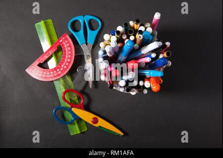 pens pens pencils ruler and scissors in a plastic jar on a dark background - Stock Photo