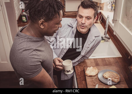 A gay couple sharing stories from their day at work over a slice of toast and a cup of tea and coffee in the evening. - Stock Photo