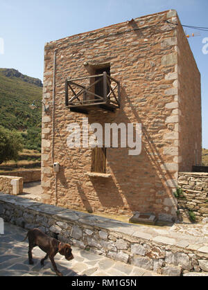 Brown dog under tower village house in Mani, Greece. - Stock Photo