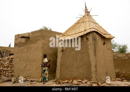 Mali, Dogon Country. Adobe barns in the village of Daga. Woman carrying son. - Stock Photo