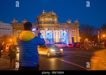 Man taking photos of Alcala Gate, night view. Madrid, Spain. - Stock Photo
