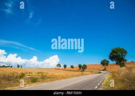 Side road and cloudy sky. Hita, Guadalajara province, Castilla La Mancha, Spain. - Stock Photo
