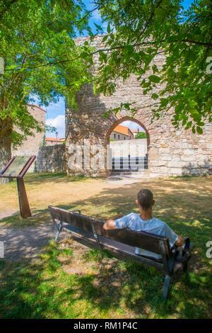 Man sitting on bench at Arab Gate. Medinaceli, Soria province, Castilla Leon, Spain. - Stock Photo