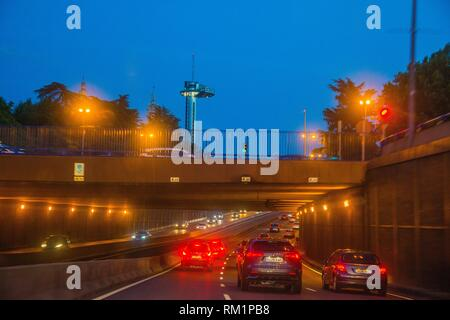 Traffic in A6 highway, bridge and Faro de Moncloa, night view. Madrid, Spain. - Stock Photo