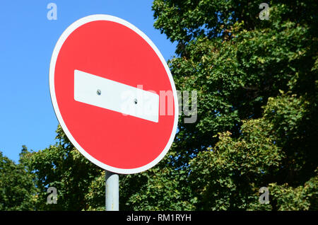 A circular red sign with a white bar indicating NO ENTRY on a grey metal post against a green trees and blue clear sky - Stock Photo