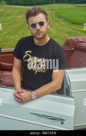 Super papa in luxus oldtimer. Turkish ethnicity. Blogger Adem Bayalan. Bavaria, Germany. - Stock Photo