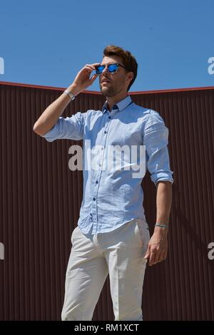 Portrait of Youtuber Axel Sprenger touching sunglasses. In Germany, Bavaria. - Stock Photo