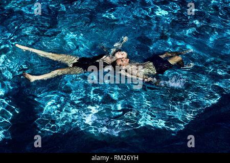 Greece, Crete, Chersonissos, couple floating in sea water - Stock Photo