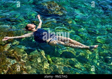 woman floating in sea water, wearing dress and slip, in holiday destination Chersonissos, Crete, Greece - Stock Photo