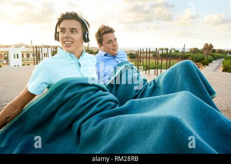Two young men sitting on the floor, under blanket, in holiday destination Malia, Crete, Greece - Stock Photo