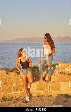two friends sitting on ancient ruins at seaside, hanging out. In Chersonissos, Crete, Greece - Stock Photo