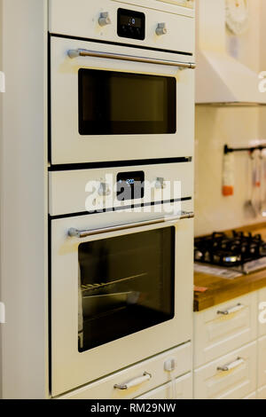 Elegant kitchen interior with white, gray furniture.Modern interior of kitchen with electric stove and oven. Patterned tile floor and wall in the - Stock Photo