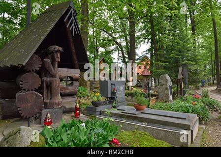 representation of ´´Worried´´ or ´´Distressed´´ Christ, related to the Polish folk culture, on wooden funerary stela in the old cemetery of Zakopane, - Stock Photo