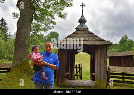 woman holding her child at the entrance of the Greek Catholic church of St. Paraskevia in the village of Nowica, commune of Uscie Gorlickie, Gorlice - Stock Photo