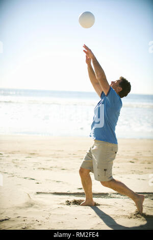 Mid-adult man playing volleyball on a beach. - Stock Photo