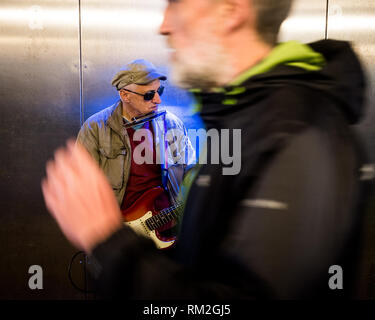 Male busker fort william underpass entertains as strangers pass by - Stock Photo