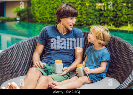 Father and son eat dessert with chia seeds and mangoes by the pool in the morning. healthy eating, vegetarian food, diet and people concept - Stock Photo
