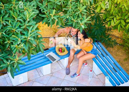 young couple taking selfie while sitting on bench in park. Greek ethnicity. In late summer / September. In Hersonissos, Crete, Greece - Stock Photo
