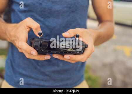 Man holds remote controller with his hands and controls the drone. New technologies and innovations concept - Stock Photo