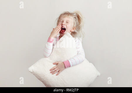 Healthy sleep concept. Cute blonde Caucasian girl child in pink pajamas with closed eyes yawning covering wide open mouth with palm. Sleepy kid with m - Stock Photo