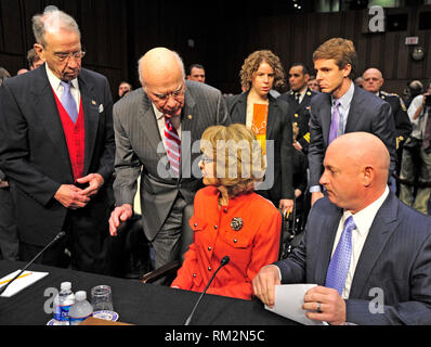 United States Senator Chuck Grassley (Republican of Iowa), left, the Ranking Member, and Chairman Patrick Leahy (Democrat of Vermont), left center, checks former U.S. Representative Gabrielle Giffords (Democrat of Arizona), lower center, at the witness table as she prepares to read a statement before U. S. Senate Committee on the Judiciary hearing entitled ?What Should America Do About Gun Violence?? on Capitol Hill in Washington, D.C. on Wednesday, January 30, 2013. Her husband, Captain Mark Kelly, United States Navy (Retired), representing Americans for Responsible Solutions, right, accompan - Stock Photo