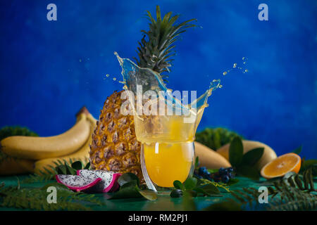 Fresh juice dynamic splash. Tropical fruits, bananas, pineapple, and dragon fruit. Exotic drink action photography with copy space - Stock Photo