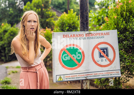 BALI, INDONESIA - 21 May, 2018: Young woman looks at protest sign on a wall in Indonesian objecting to Uber and Grab taxi drivers reads 'Uber and Grab - Stock Photo