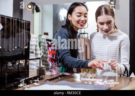 Brunette beautiful asian woman in a navy polo neck and her friend spending time together - Stock Photo