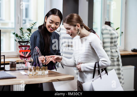Brunette beautiful asian woman in a navy polo neck and her friend discussing adornments