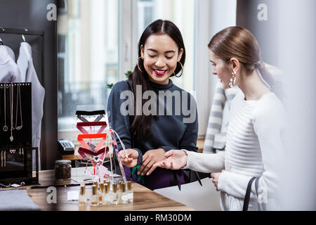 Dark-haired smiling asian woman in a navy polo neck testing a new perfume - Stock Photo