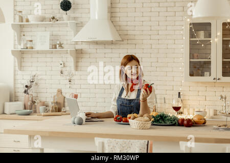 Beautiful young red-haired girl with big earrings holding a red pepper in her hand - Stock Photo