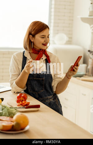 Red-haired young girl with piercing in her nose holding a phone in her hands - Stock Photo
