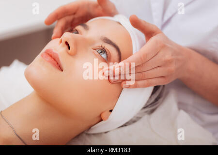 Face of a pleasant young woman during facial massage - Stock Photo