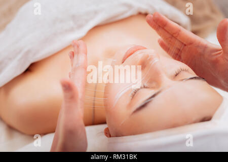 Nice pleasant woman having a special cream applied on her skin - Stock Photo